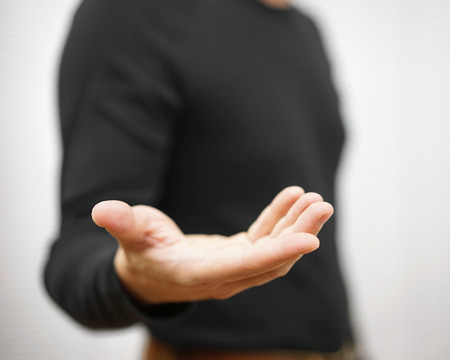 hand out: male is standing  and shows outstretched hand with open palm