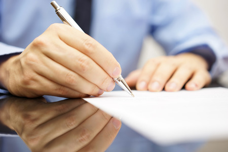 financial agreement: businessman is writing a letter or signing a agreement