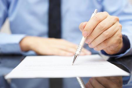 ビジネスマンは契約の保険金詐欺を検索します。 写真素材