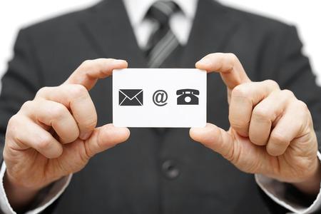 ビジネスマンは、電子メール、メール、電話のアイコンでのビジネス カードを保持します。お問い合わせ