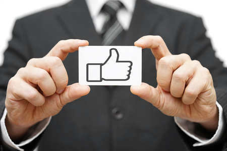 businessman hold business card with thumbs up icon photo