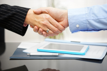 male hands: businessman and businesswoman are handshaking over documents and presentation
