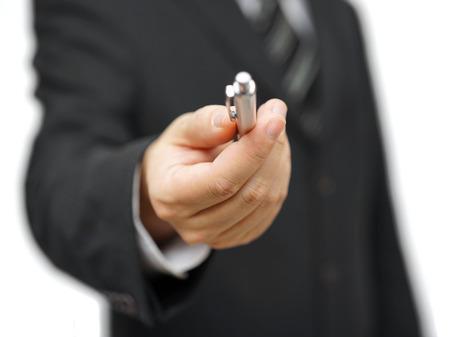 Closeup of businessman offering a pen Standard-Bild