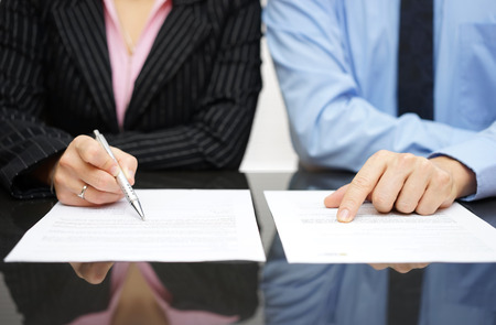 business review: businessman and businesswoman are inspecting  contract