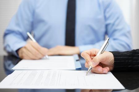 Man en vrouw ondertekening van een zakelijk contract na de afronding van de onderhandelingen