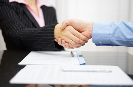 manager office: business partner and client  are handshaking over signed contract Stock Photo