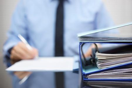 bindmiddelen met papieren wachten om te worden verwerkt met zakenman terug in vervagen. Boekhouding en business concept Stockfoto