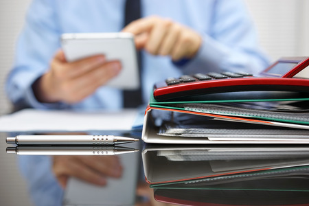 files and folders and businessman in background with tablet pc in hands