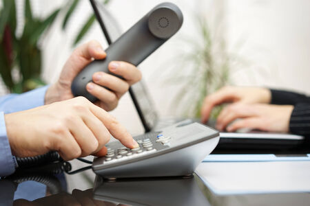 contact info: businessman and woman are contacting new clients  over telephone and internet Stock Photo