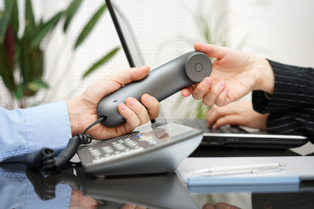 PHONE LINE: Businessman  gives woman handset. teamwork and customer support concept