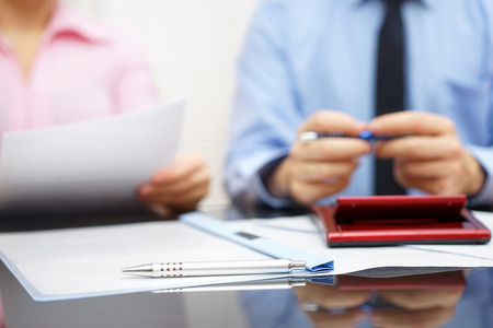 advice: businesswoman is reading contract to businessman in blur background, focus is on pen