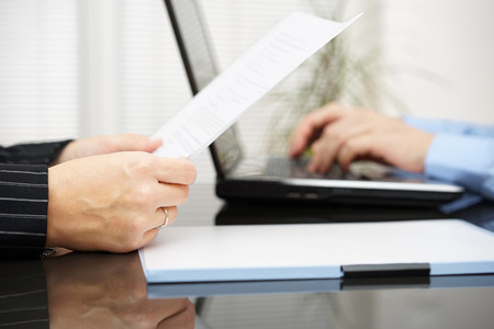legal advice: lawyer is reading contract and bussiness client is typing on laptop