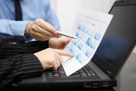 Mensen uit het bedrijfsleven tijdens de vergadering bespreken en te wijzen op de financiële diagram, grafieken