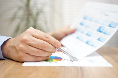 financial adviser: Financial adviser is reviewing report with charts and graphs