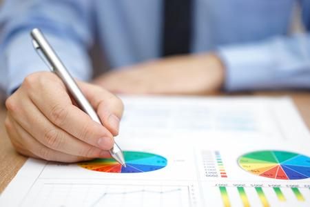Geschäftsmann ist der Analyse von Geschäftsbericht mit Grafiken und Diagrammen