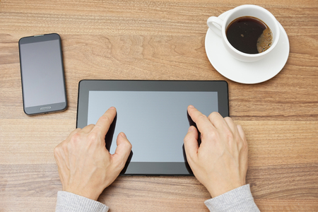 fingers on top: young adult is typing with two fingers on tablet computer, top view Stock Photo
