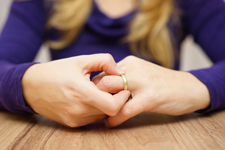 relationship breakup: woman is taking off the wedding ring Stock Photo