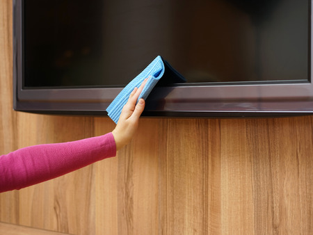 Cleaner from cleaning service is cleaning dirt and dust from tv and furniture photo