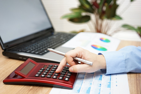 refinance: businessman analyzing business data with calculator,laptop,reports