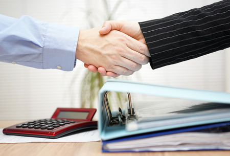 business law: businessman and businesswoman are handshaking over binders Stock Photo