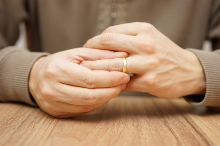 relationship breakup: Man is taking off the wedding ring Stock Photo