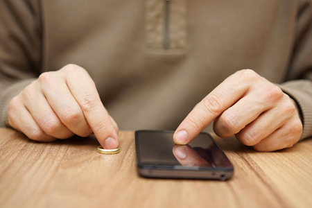 husband: Man is flirting with another woman over mobile phone to go on date without wedding ring. Cheating concept