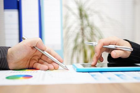 Zakelijke collega's samen te werken aan het project met een tablet-computer en papier verslag Stockfoto