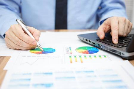 사업가 비즈니스 데이터를 분석하고 노트북을 사용하고 있습니다