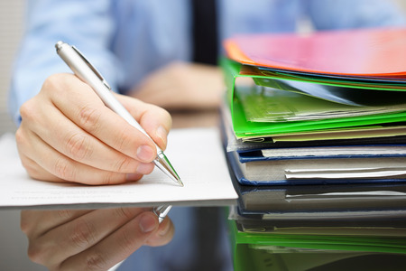 financial audit: businessman is writing on document and a lot of documentation is waiting to be reviewed Stock Photo