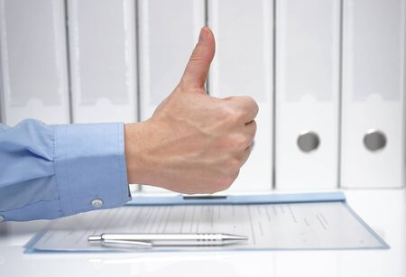 hidden success: thumbs up over signed contract and binders Stock Photo