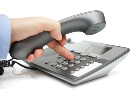 contact person: Businessman finger pressing a number button on the land line telephone