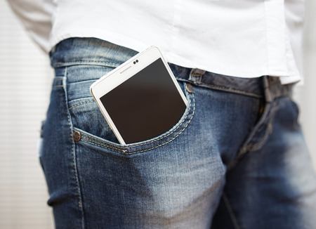 big white smart mobile phone in jeans pocket