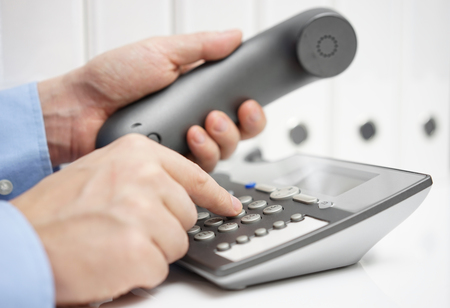 numpad: Businessman is dialing phone for advice