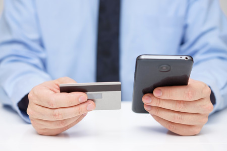 application software: Businessman is buying application  with  credit card on mobile phone Stock Photo
