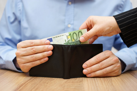 give: Woman is taking money out of a husbands wallet