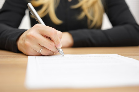 conclusion: Woman with black shirt is signing legal document
