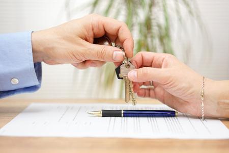 contratos: agente de bienes raíces le da las llaves de casa a su cliente después de la firma del contrato Foto de archivo