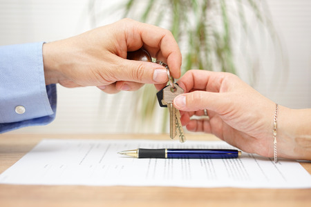 estate: real estate agent gives house keys to his client after signing contract