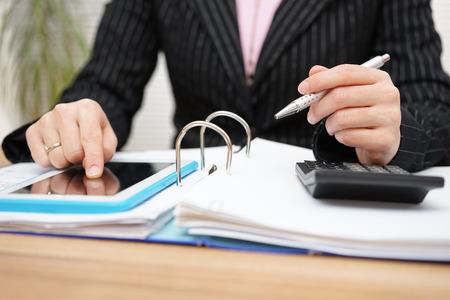 impuestos: contable de sexo femenino mediante la asistencia en el PC tableta para completar el trabajo