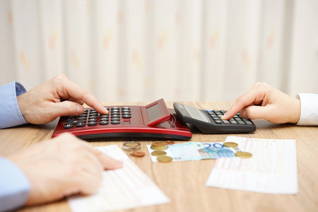 husband and wife are calculating monthly expenses. tight budget concept