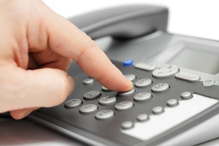 closeup of finger dialing on telephone. customer support concept Standard-Bild