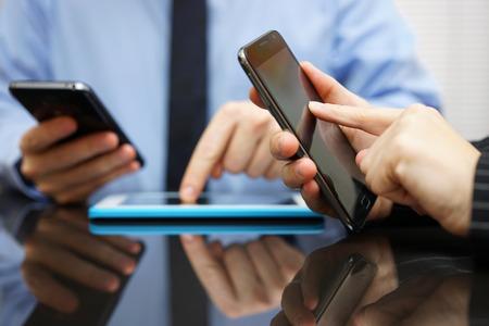 Geschäftsmann und Geschäftsfrau arbeiten und unter Einsatz von intelligenten Handys und Tablet-Computer im Tagungs