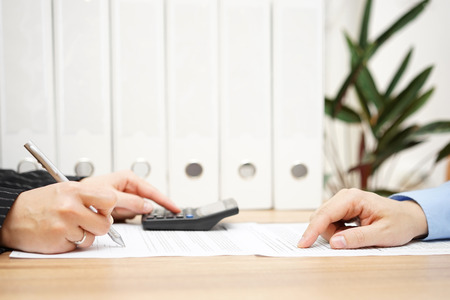 financial agreement: businessman and businesswoman are analyzing financial numbers on document