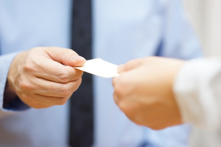 businessman and businesswoman are exchanging business cards