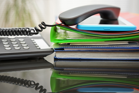 unorganized: telephone handset and tablet pc on top of the documentation in office