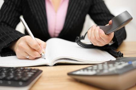 secretarias: secretaria ocupada está contestando llamadas y escribir notas al mismo tiempo, Foto de archivo