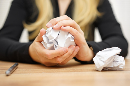 successful woman: Hands of woman crumple sheets of paper at the table