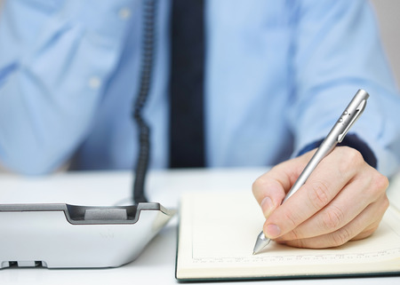 interview: Businessman is talking on the phone and writing memo Stock Photo