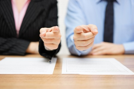 staffing: businessman and businesswoman pointing with fingers to you. Staffing and recruitment concept