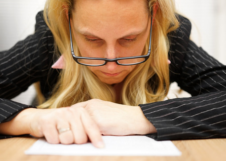 small articles: woman with glasses reading document very precise and pointing to text